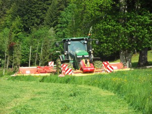 Tracteur 7230R accouplé à la faucheuse combinée Pöttinger qui permet de faucher sur une largeur de 10.50 mètres.